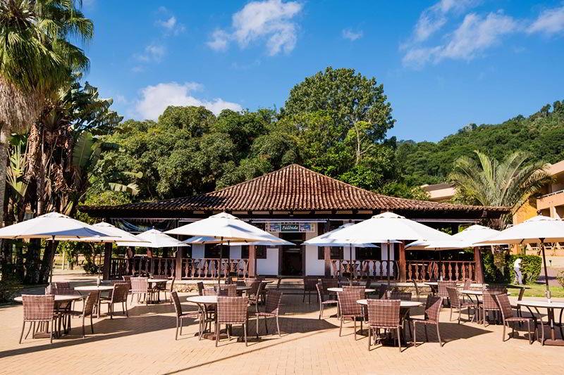 Fachada com guarda sol e cadeiras na parte externa do Restaurante da Fazenda