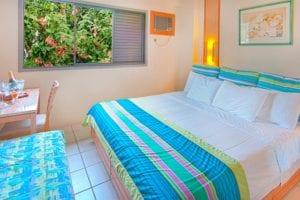 Quarto Standard vista para resort contendo uma cama casal , sofá e mesa para refeições
