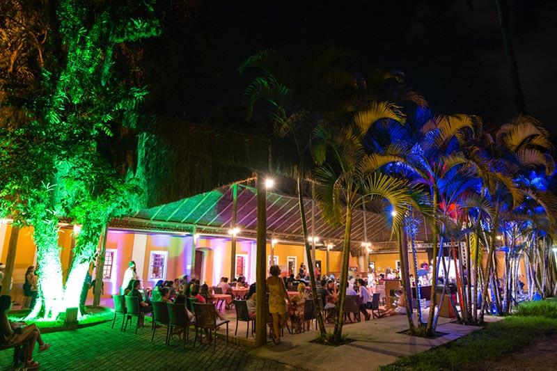 Sapê restaurante parte externa durante a noite com cadeiras e iluminação charmosa